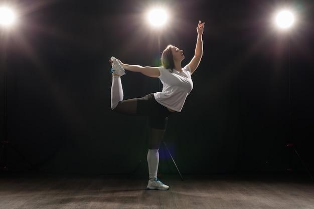 검은 스튜디오 배경에서 재즈 펑크 춤을 추는 젊은 아름다운 슬림 여성.