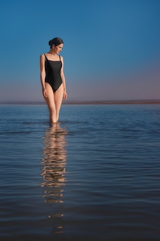 Young beautiful slim woman wearing a black swimsuit stands in the sea and watching sunset