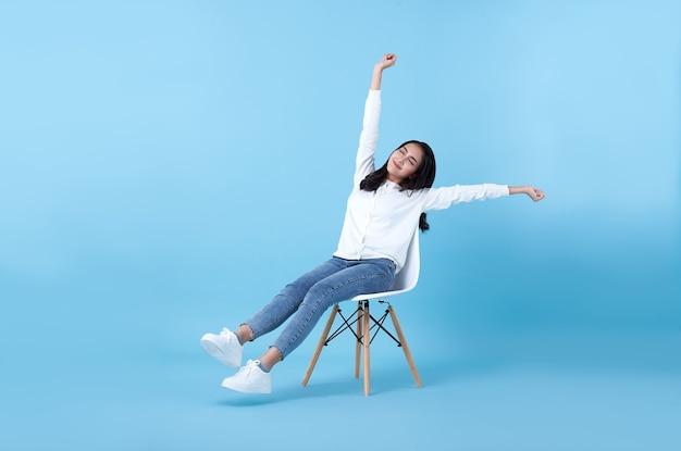Giovane bella ragazza asiatica sorridente che si rilassa seduta sulla sedia sull'azzurro.