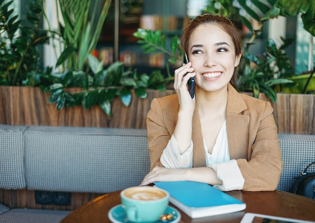 緑のカフェで携帯電話を使用してベージュのスーツで若い美しい笑顔のアジアの女の子の学生