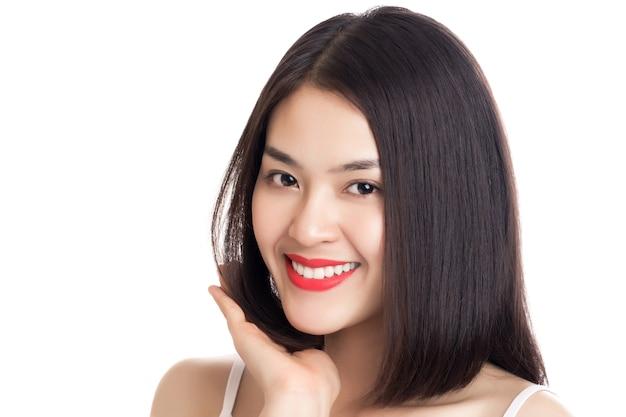 Молодая красивая улыбающаяся азиатская женщина с рукой, касаясь ее волос, изолированных на белом.