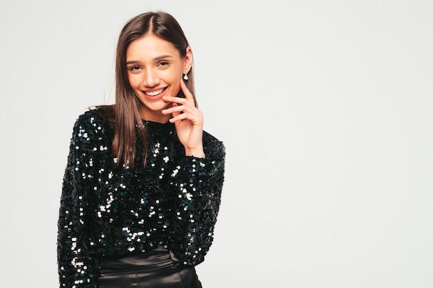 Молодая красивая улыбающаяся брюнетка в красивой модной черной вечерней одежде