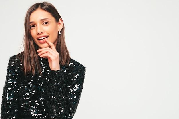 Giovane bella donna bruna sorridente in bei vestiti da sera neri alla moda