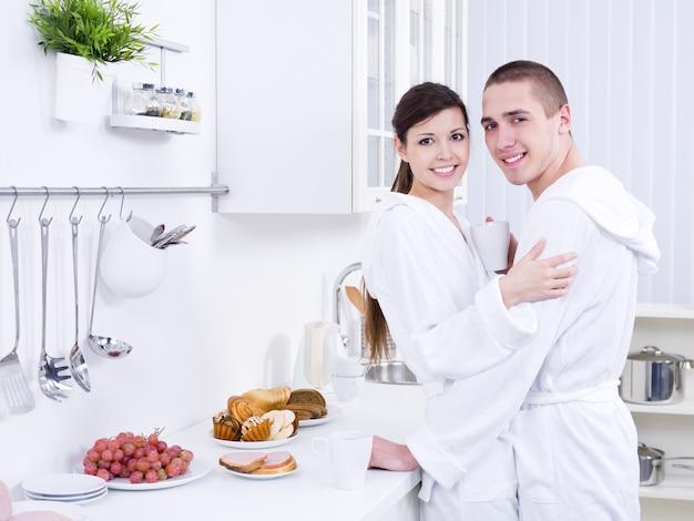 Молодая красивая улыбающаяся пара, обнимающаяся на кухне