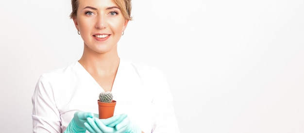 Young beautiful smiling female beautician holding a small cactus in a pot