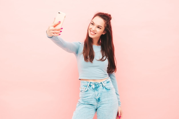 Young beautiful smiling female in trendy summer hipster clothes