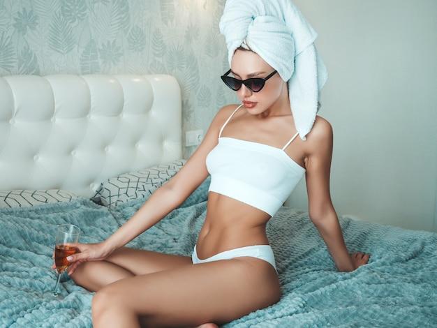 Giovane bella donna sorridente in biancheria bianca e asciugamano sulla testa