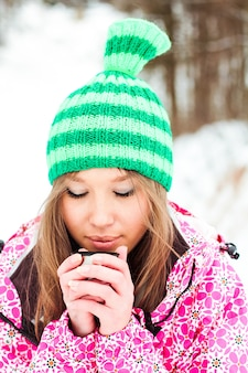 Young beautiful smiling girl in a crimson jacket and green hat drinking hot tea from a thermos in snowy mountains