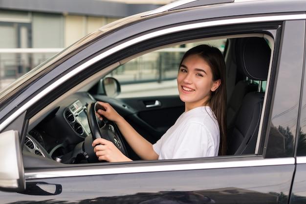 Молодая красивая улыбающаяся девушка за рулем автомобиля на дороге