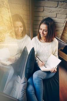 Молодая красивая улыбающаяся девушка в белом свитере и джинсах сидит на подоконнике и рисует картину в альбоме