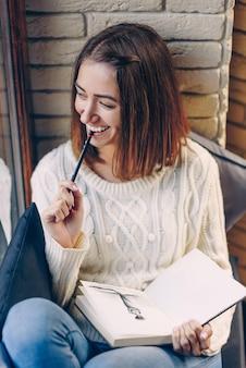 Молодая красивая улыбающаяся девушка в белом свитере сидит на подоконнике и рисует картину в альбоме