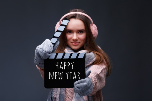 Young beautiful smiling girl in knitting pullover holding director's clapper board