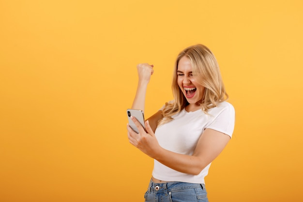 Young, beautiful, smiling girl looks at the phone and makes a winner gesture