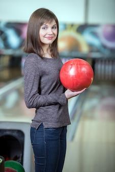 Young beautiful smiling girl playing bowling.