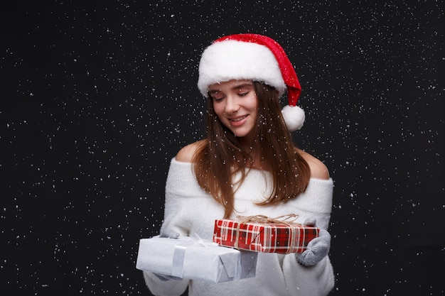 Young beautiful smiling girl in red santa hat holding gift boxes
