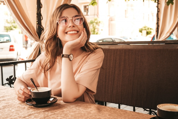 Молодая красивая улыбающаяся девочка битник в модной летней одежде. беззаботная женщина, сидя в кафе на террасе веранды и пить кофе. позитивная модель с удовольствием и мечты