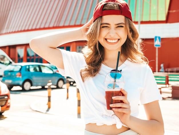キャップの若い美しい笑顔の流行に敏感な女性。通りでポーズをとって夏の流行の服の女の子