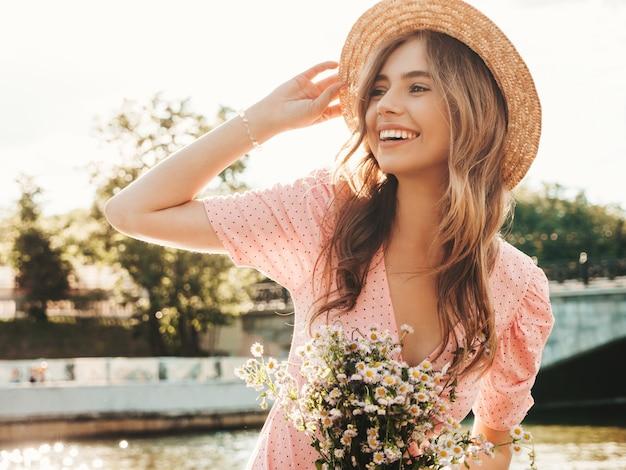 トレンディな夏のサンドレスで若い美しい笑顔の流行に敏感な女性