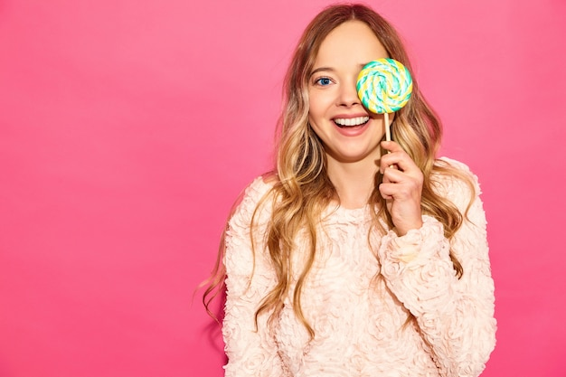 Young beautiful smiling hipster woman in trendy summer clothes. sexy carefree woman posing near pink wall. positive model hiding her eye by lollipop