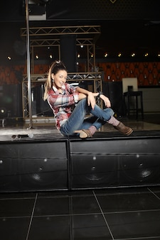 Young beautiful smiling pop star singer with microphone sitting on the scene in the club
