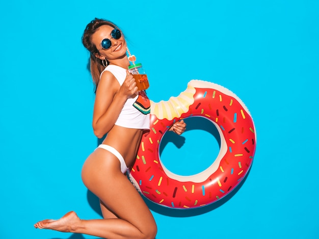 Young beautiful smiling sexy woman in sunglasses. girl in white summer underpants and topic with donut lilo inflatable mattress. . drinking fresh cocktail smoozy drink