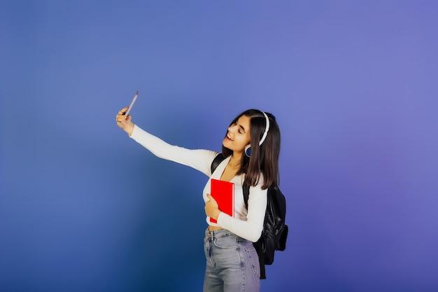 黒のバックパックとヘッドフォンを持った若い美しい笑顔の学生の女の子は、青い表面で彼女の携帯電話で自分撮りをします。