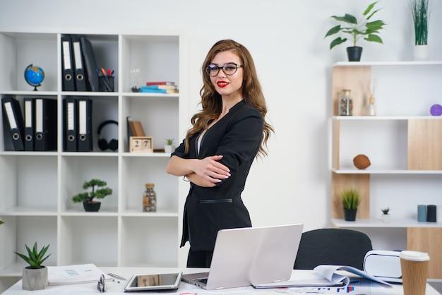 オフィスでのビジネススーツで若い美しい笑顔の女性。