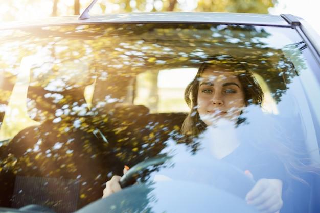 車を運転して若い美しい笑顔の女性