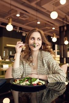 건강 한 음식을 먹는 젊은 아름 다운 웃는 여자