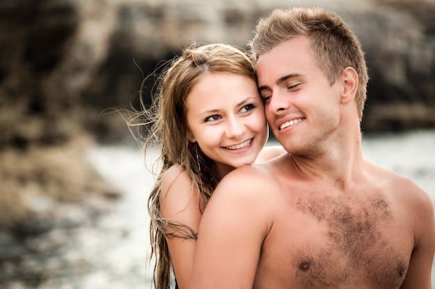맑은 여름 날에 배경에서 자연 바위와 그녀의 행복한 남자 친구 뒤에서 껴안은 젊은 아름 다운 웃는 여자
