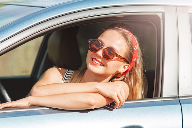 Young beautiful smiling woman hipster girl in sunglasses driving new car on sunny summer day.