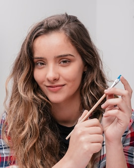 Young beautiful smiling woman holding paintbrush looking at camera