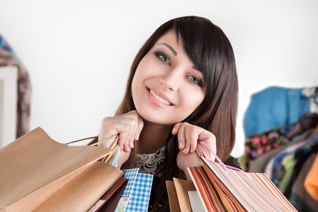 購入すると紙袋を保持している若い美しい笑顔の女性。販売とショッピングのコンセプト