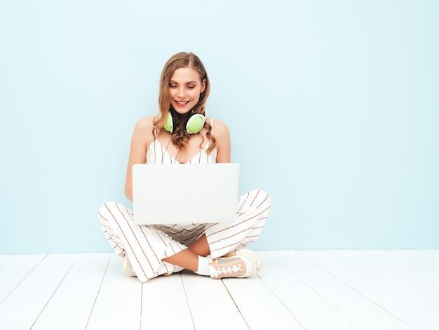 トレンディな夏の流行に敏感なオーバーオールの服を着た若い美しい笑顔の女性