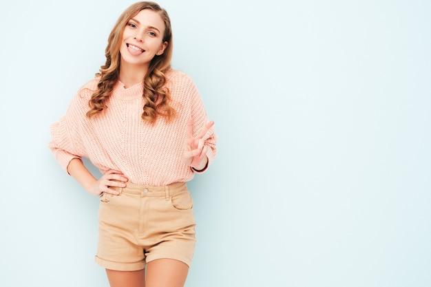 トレンディな夏のスーツの服を着た若い美しい笑顔の女性。スタジオで水色の壁の近くでポーズをとるセクシーな屈託のない女性