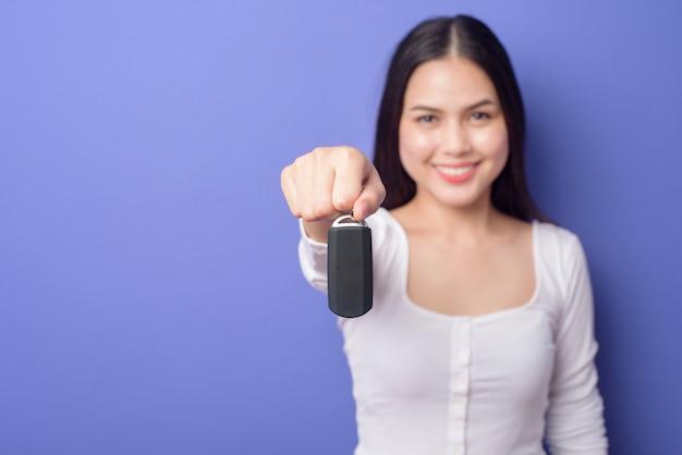 Молодая красивая усмехаясь женщина держит ключ автомобиля над изолированным пурпуром