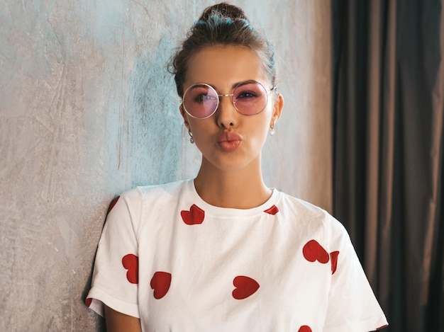 Young beautiful smiling woman looking at camera  trendy girl in casual summer white dress and sunglasses    making duck face