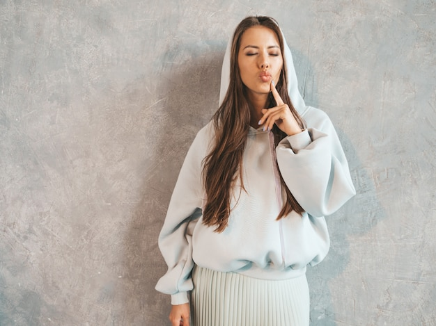 Young beautiful smiling woman looking . trendy girl in casual summer hoodie and skirt clothes.  making duck face