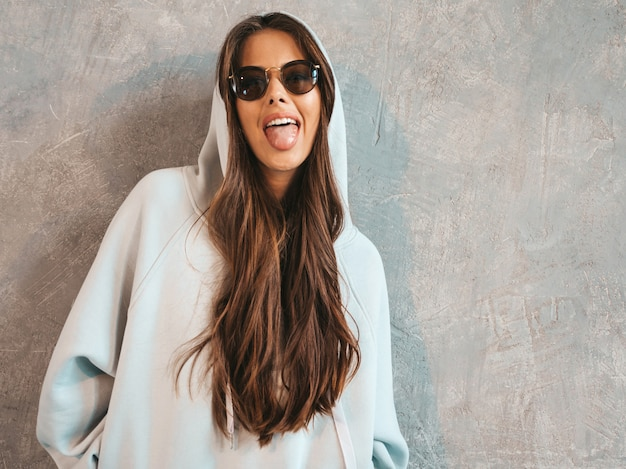 Young beautiful smiling woman looking . trendy girl in casual summer hoodie and skirt clothes.  .shows tongue