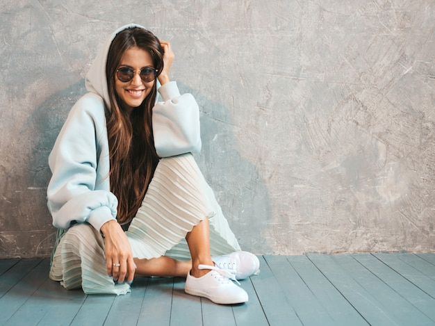 Young beautiful smiling woman looking . trendy girl in casual summer hoodie and skirt clothes.   sitting on the floor