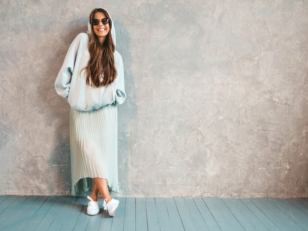 Young beautiful smiling woman looking . trendy girl in casual summer hoodie and skirt clothes.   in sunglasses