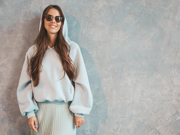 Young beautiful smiling woman looking . trendy girl in casual summer hoodie and skirt clothes.