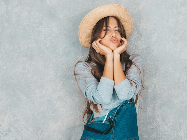 Young beautiful smiling woman looking . trendy girl in casual summer overalls clothes and hat.  making duck face