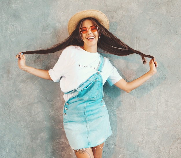 Young beautiful smiling woman looking . trendy girl in casual summer overalls clothes and hat. . playing with her hair