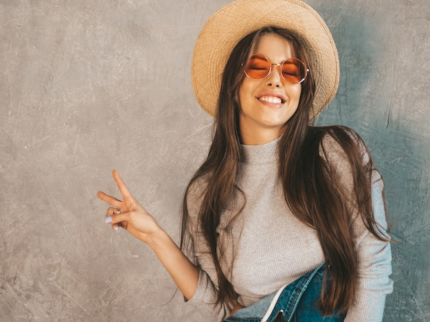 Young beautiful smiling woman looking . trendy girl in casual summer overalls clothes and hat. shows peace sign