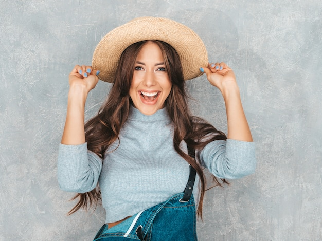 Young beautiful smiling woman looking  . trendy girl in casual summer overalls clothes and hat.