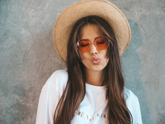 Young beautiful smiling woman looking . trendy girl in casual summer t-shirt clothes and hat.. giving air kiss