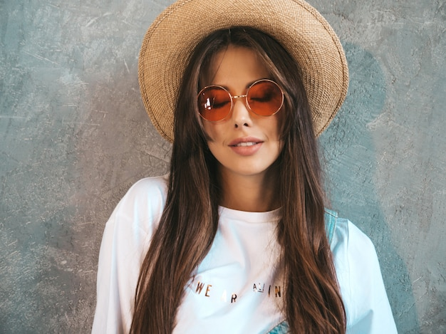Young beautiful smiling woman looking . trendy girl in casual summer t-shirt clothes and hat.