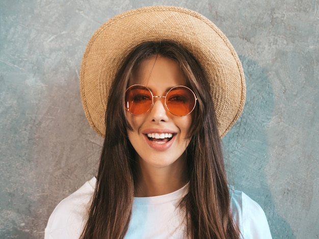 Young beautiful smiling woman looking . trendy girl in casual summer t-shirt clothes and hat..
