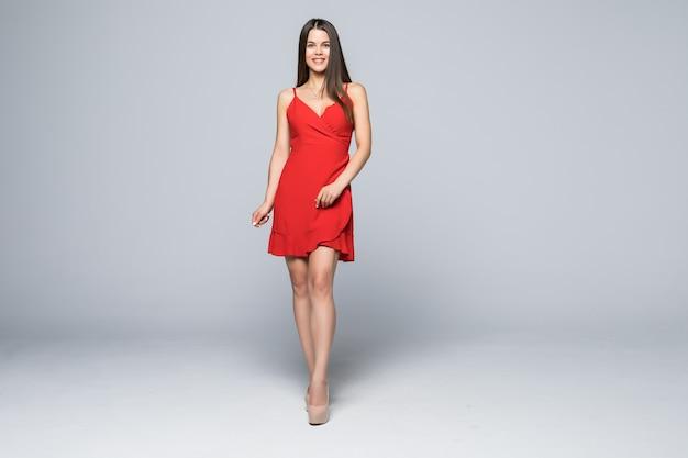 Giovane bella donna sorridente in abito rosso sul muro bianco